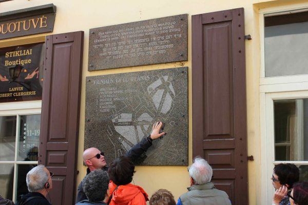 Private tour guide explains the location using a stone map on the wall of the building in Vilnius Ghetto