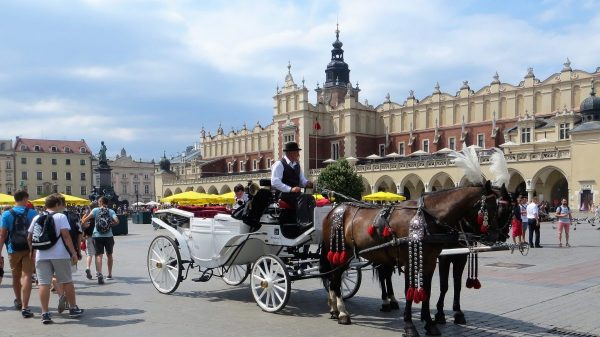 A horse and a white carriage with a traditionally dressed carriage-men in Krakow city square