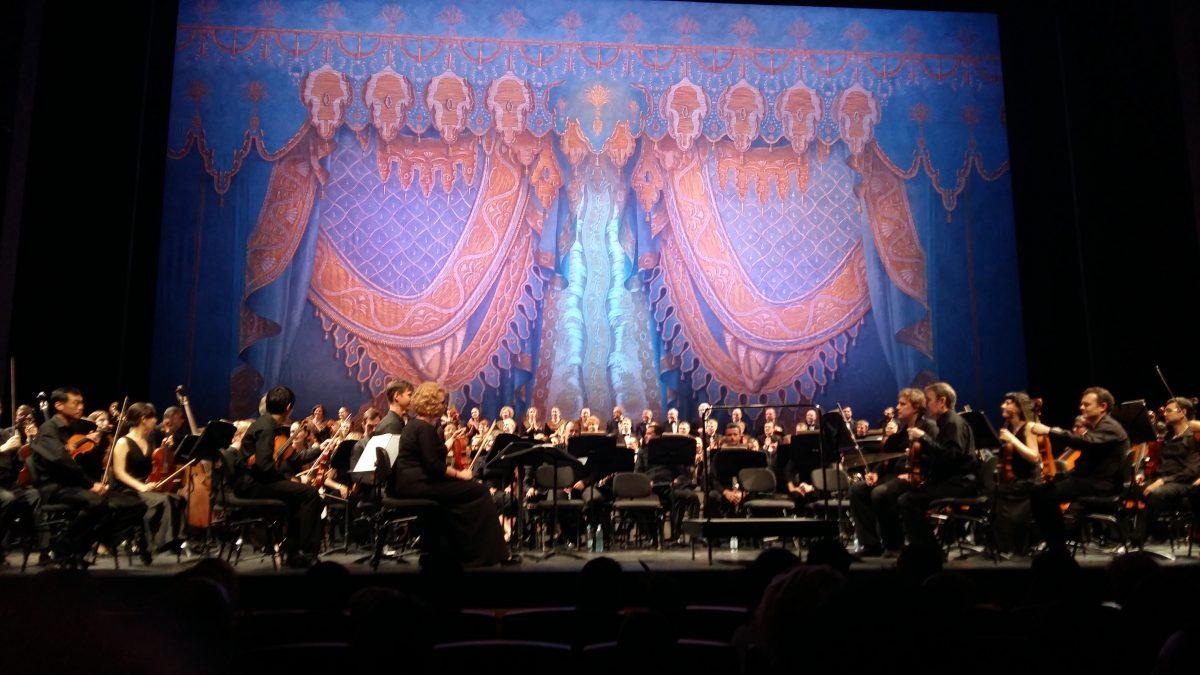 תזמורת תיאטרון מרינסקי על רקע וילון הבה מחכה למנצח