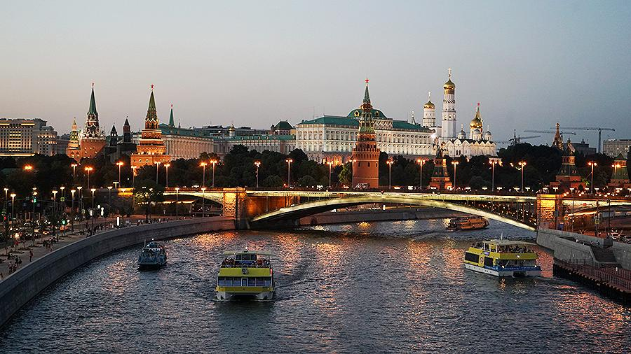 Motor boat crossing the river, on the background you see Moscow Kremlin