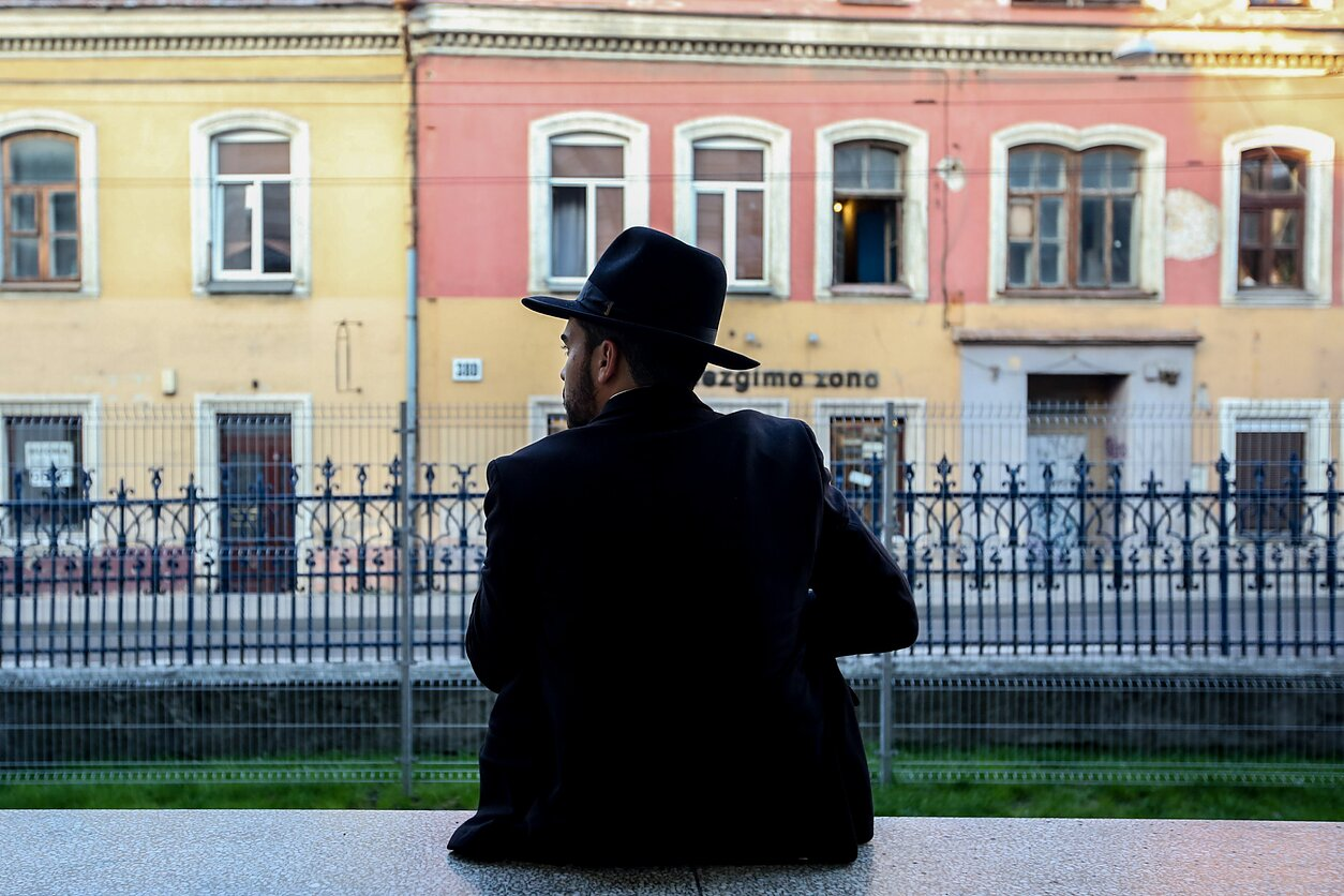 A guy in a black hat and suit sits opposite colored houses
