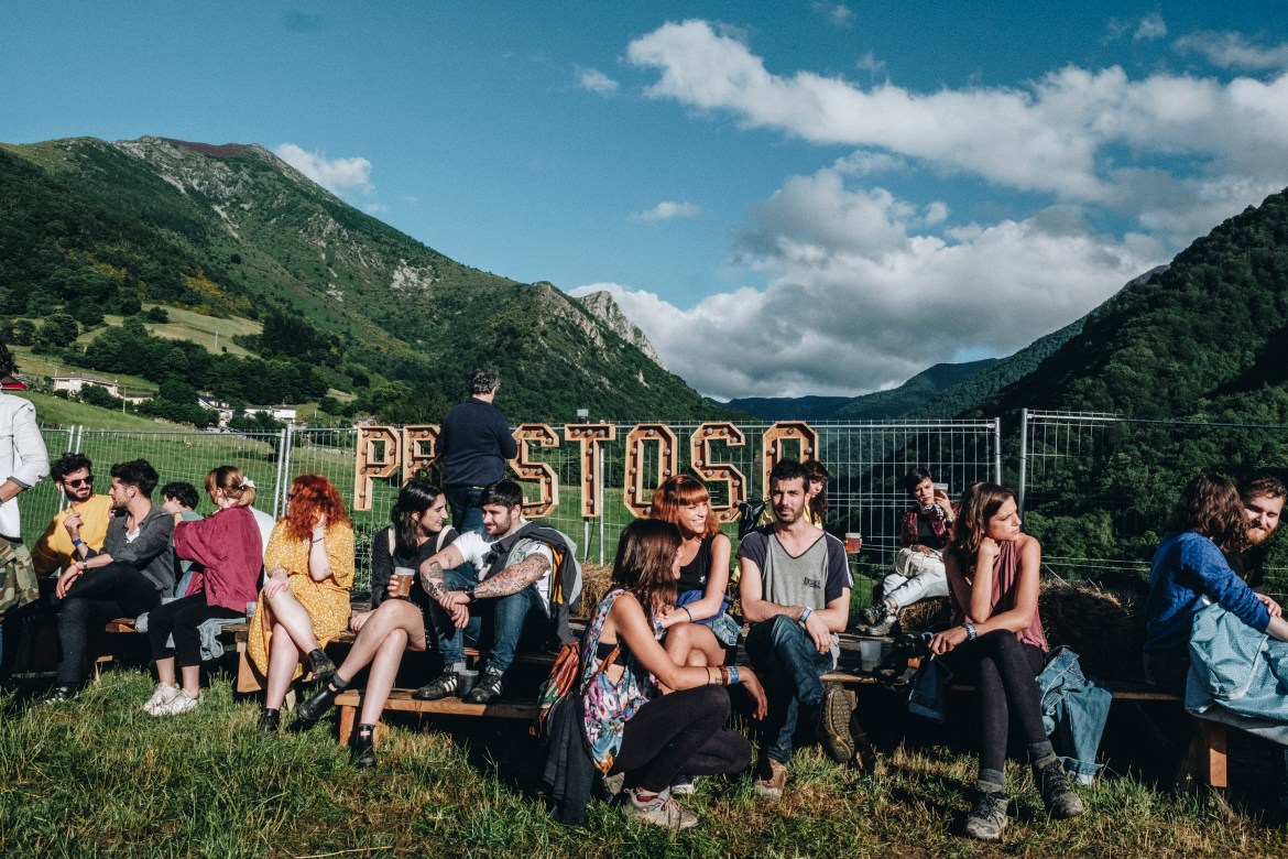A company of youth sits on the green grass near the fence. Behind the fence beautiful views of the mountains and blue sky
