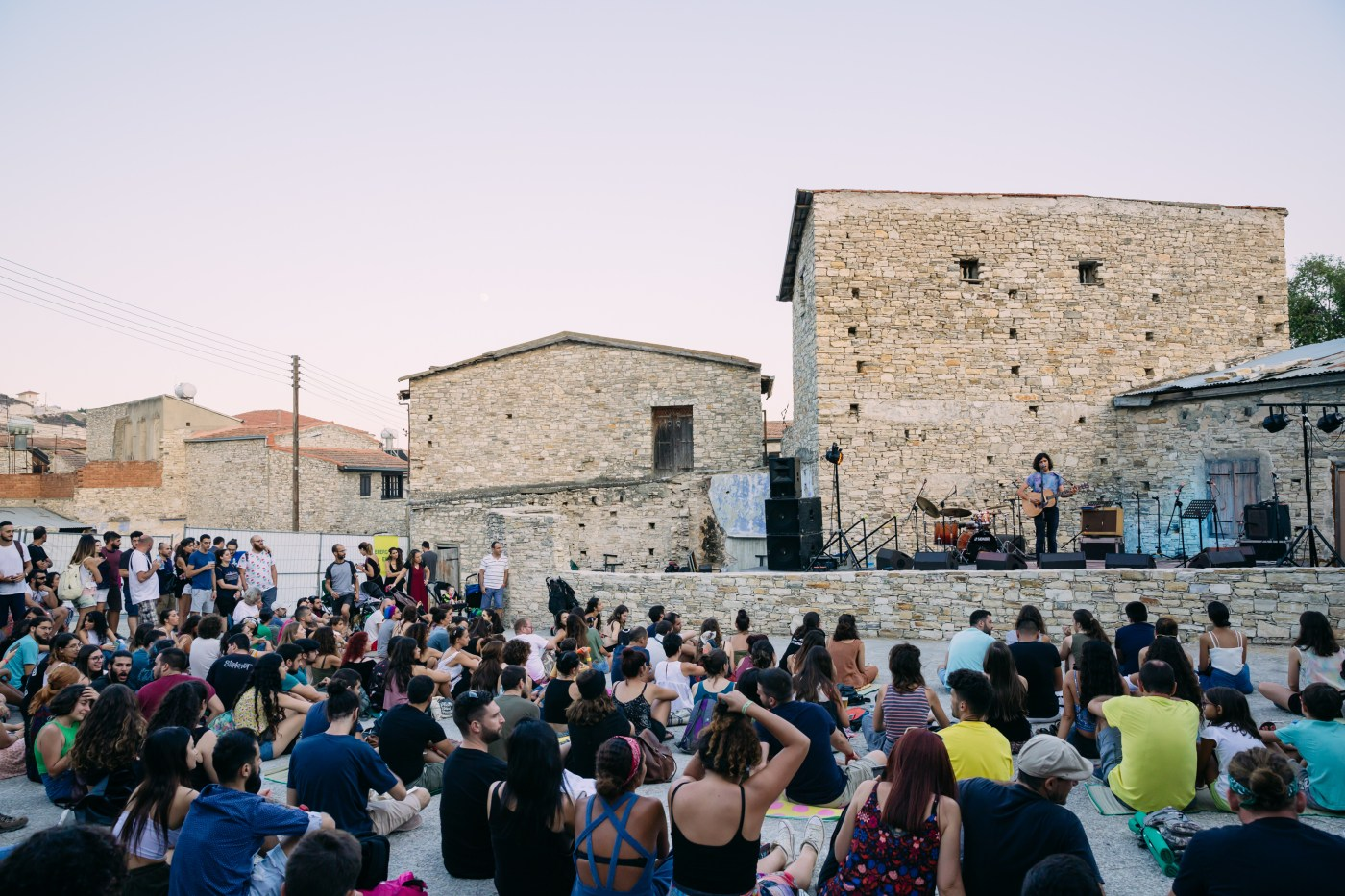 A crowd of people sits on the floor in front of the stage next to the small houses of light brick. Musicians perform on stage