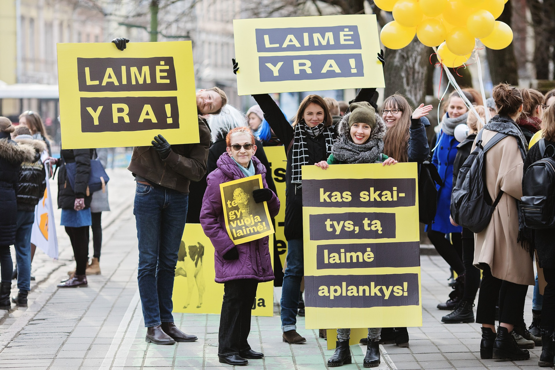 A crowd of people in winter clothes is standing with yellow-black posters that say Happiness is in Lithuanian
