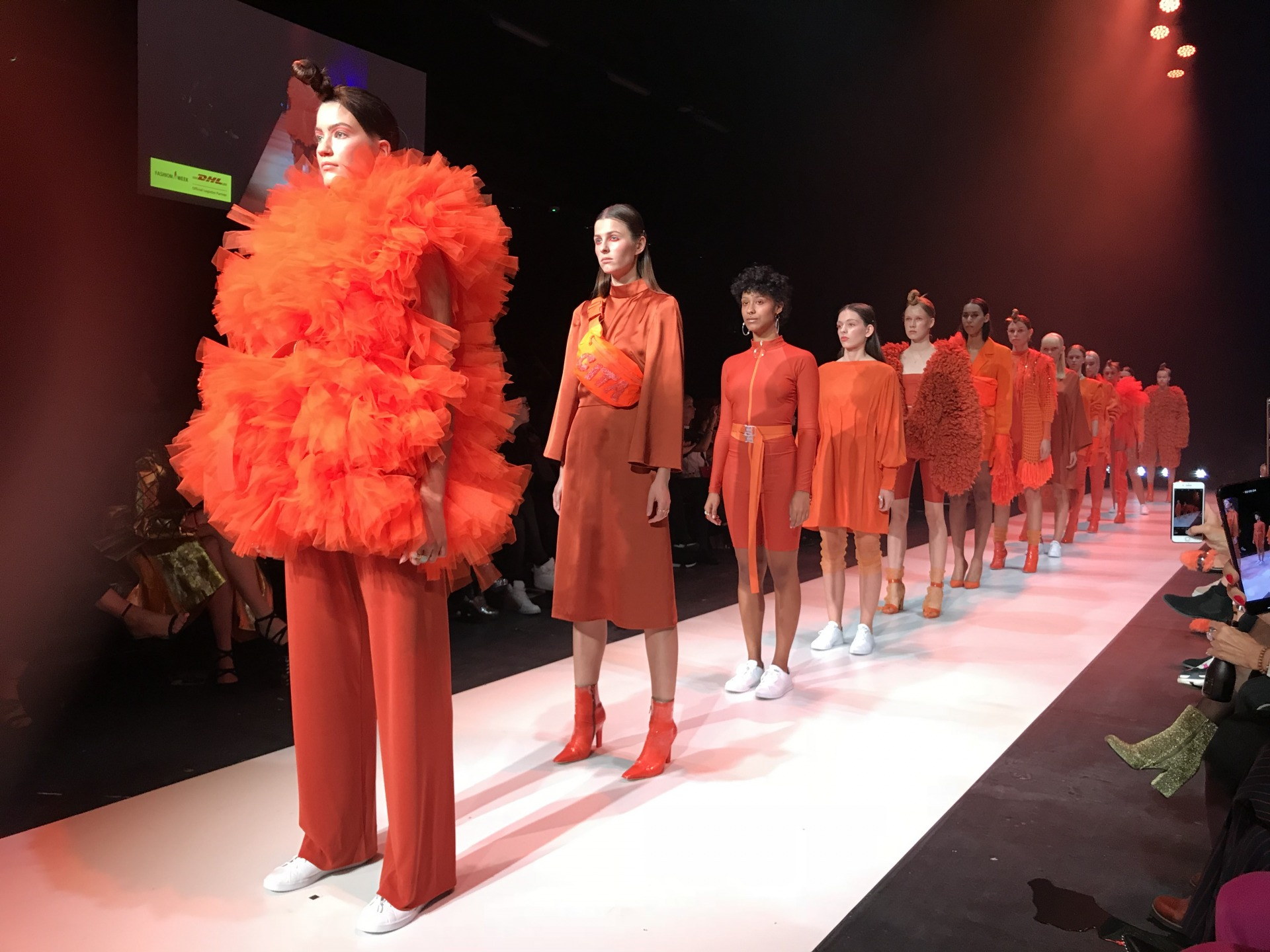 Girls in bright orange dresses stand next to each other on the catwalk