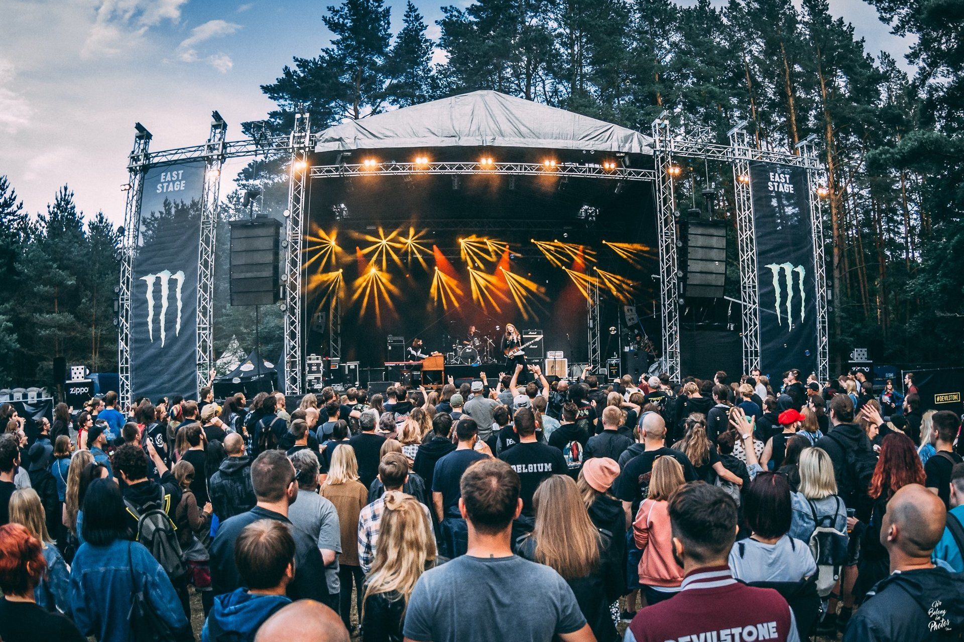 A crowd of people faces a huge scene in the forest