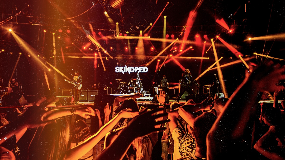 On stage, musicians play a concert amid Skinred's sign, a crowd of people dancing and waving their arms under orange spotlights